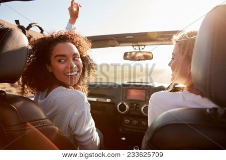 Two girlfriends driving with sunroof open, one turning round