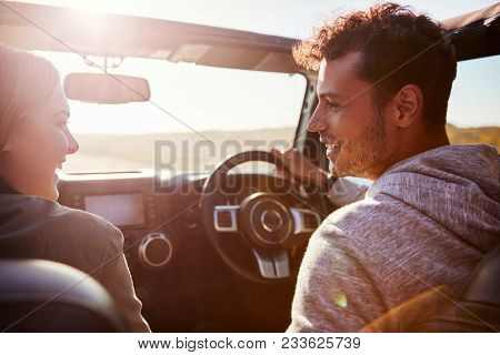 Happy couple driving in car with sunroof open, passenger POV