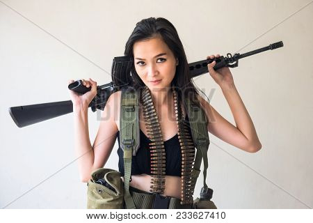 Young Asian Sexy Woman In Soldier Uniform Holding An Assault M16 Rifle Gun With Many Bullets And  Va