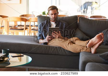 Attractive Young White Man Sitting Comfortably On His Great Couch With His Feet Up While Surfing The