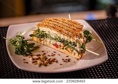 Delicious Sandwich With Chicken And Rocket Served On A White Plate