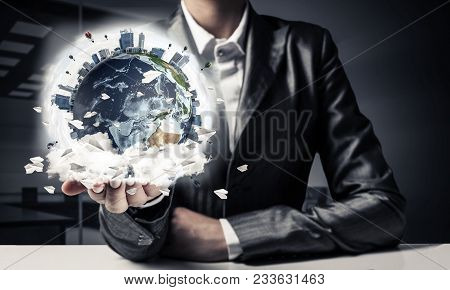 Closeup Of Businessman In Suit Keeping In Hands Earth Globe With Buildings And Flying Paper Planes.