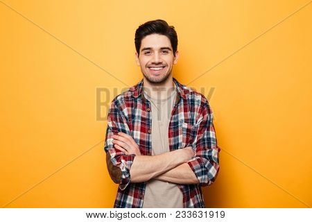 Portrait of a smiling young man standing with arms folded isolated over yellow background