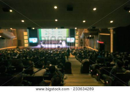 Abstract Blurred Photo Of Conference Hall Or Seminar Room With Attende Background In With Low Light