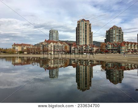 Mirrored Reflection Of High-rise Buildings Overlooking Calm Lake Water In Kelowna, British Columbia