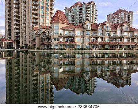 Mirrored Reflection Of Buildings Overlooking Calm Lake Water In Kelowna, British Columbia