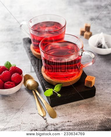 Steaming Hot Raspberry Tea In Two Transparent Cups On A Stone Table. Fresh Berries, Cubes Of Cane Su