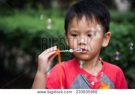 Cute Boy Blowing Soap Bubble