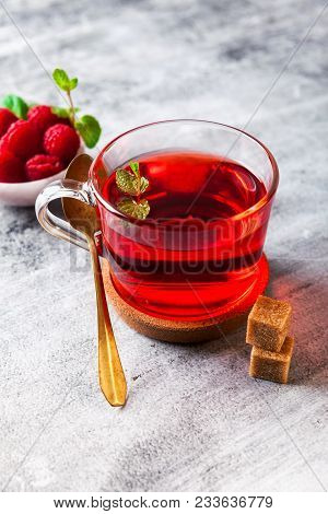 Hot Raspberry Tea In Transparent Cup On A Stone Table. Fresh Berries, Cubes Of Cane Sugar And A Bag