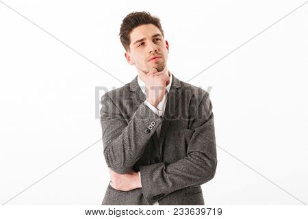 Pensive business man in jacket holding his chin and looking away over white background