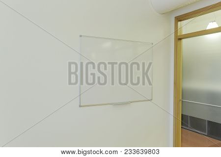 Clean White Board On White Wall In Office Room. Meeting Room. Conference Room. Business Background.