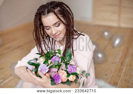 Close-up Beautiful woman with dreadlocks hairstyle holding a bouquet of flowers indoors. poster