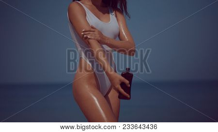 Beautiful girl in swimsuit applying sunscreen lotion tan oil on body on the tropical sandy beach during summer holiday over sea and sky background