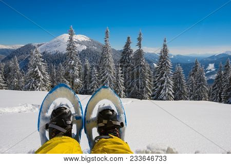 Foots Traveler In Snowshoes Against The Background Of Snow-capped Mountains On A Sunny Day. Epic Adv