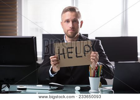 Stressed Young Businessman Holding Cardboard With Help Text In Office