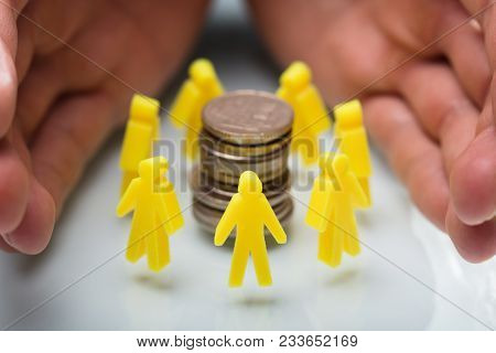 Businessperson Protecting Stacked Coins And Yellow Human Figures