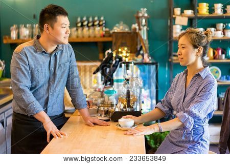 Cheerful Client And Barista Talking In Coffee House. Positive Friendly Handsome Asian Barista Brewin