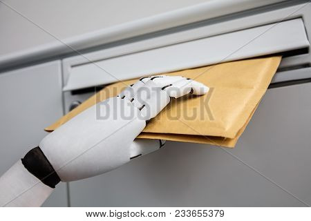 Close-up Of A Robotic Hand Inserting Envelope In Mailbox