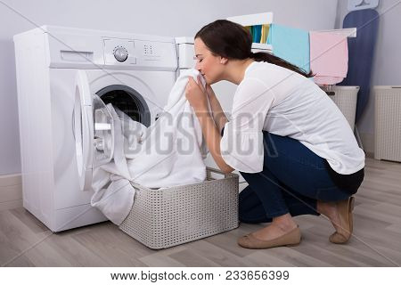 Close-up Of A Young Woman Smelling White Cloth After Washing In Washing Machine