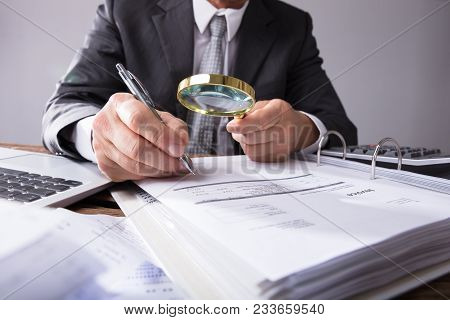 Businessperson Looking At Receipts Through Magnifying Glass