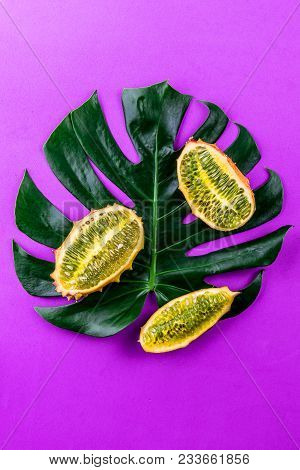 Creative Layout Made Of Summer Tropical Fruits And Tropical Leaves On Purple Background. Flat Lay. F