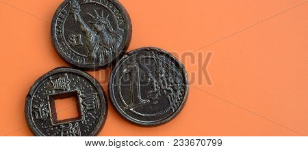 Three Chocolate Products In The Form Of Euro, Usa And Japan Coins Lie On An Orange Plastic Backgroun