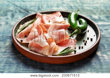 Plate With Raw Bacon Rashers And Peppers On Wooden Background