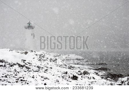 Portsmouth Harbor Lighthouise Shines During A Winter Snowstorm In New Hampshire.