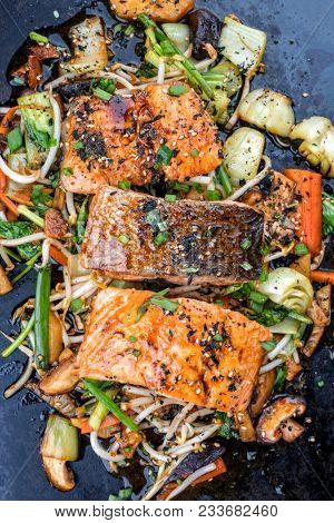 Japanese chan chan yaki with fried salmon fillet as top view on a board