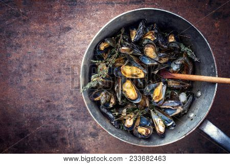 Traditional barbecue Italian blue mussel with rosemary as top view in a casserole