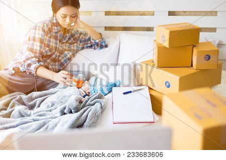 The Beautiful Single Mother Feeding Baby Milk From A Bottle, Many Packaging Stacked On The Bed With