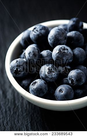 Blueberry, blueberries, fresh berry, berries, bilberry, bilberries served in a small ceramic bowl on black background