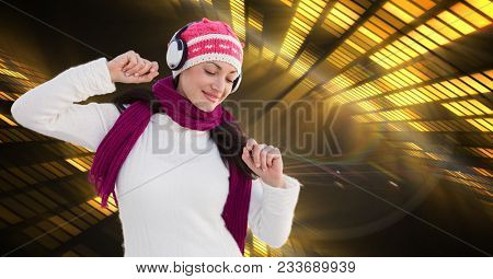 Digital composite of Woman in warm clothing listening to music through headphones