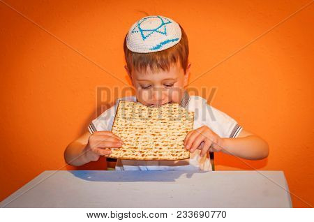 Happy Little Jewish Child With A Kippah On His Head Eating The Matzo Bread For Pessach. Passover Ill