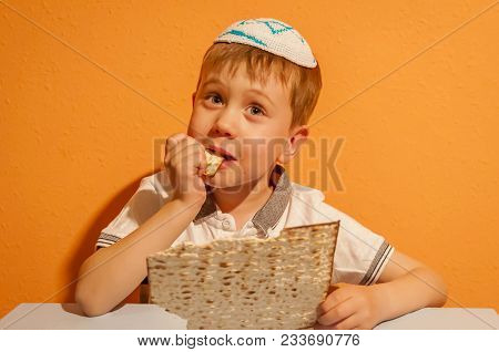 Happy Little Jewish Child With A Kippah On His Head Eating Matzo Bread And Looking Forward For The J