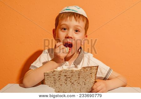 Happy Little Jewish Child With A Kippah On His Head Eating Matzo Bread. He Is Looking Forward For Th