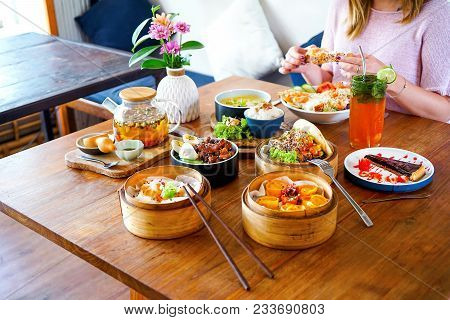 A Large, Wooden Table. A Young, Beautiful Girl In Pink Is Sitting At The Table. On The Table There A