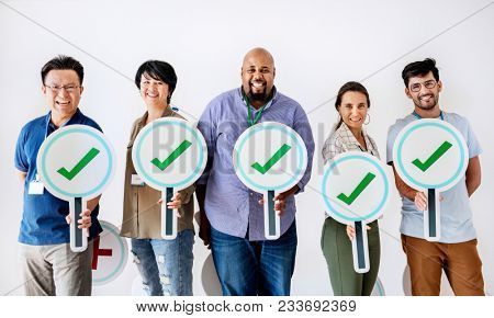 Workers standing and holding correct ticks logos