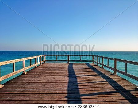 Wooden Terrace Dock Or Pier. Wooden Dock   (pier) Blue Sea And Sky Background. View Of Wooden Pier O