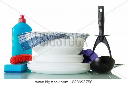 Stack Of Clean Dishes, Bottle Of Detergent, Sponge And Towel Isolated On White Background
