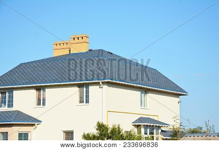 House Roof With Asphalt Shingles, Ventilation, Chimney And Roof Gutter Pipeline Outdoors. Roofing Co