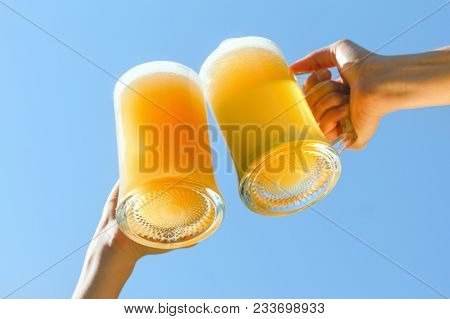 Beer Mugs Cheers, Picnic Or Party On Natural Background With Axe.