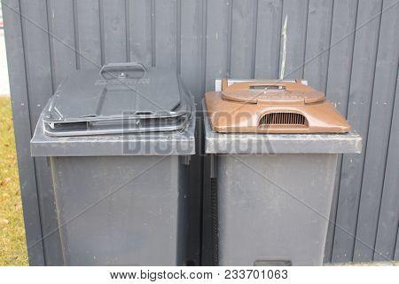 Trash Bins. Trash Cans. Black Garbage Bins Outside House.