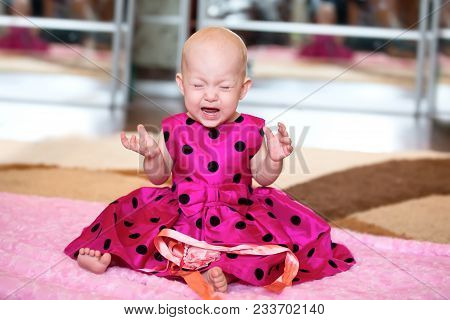 A Sobbing Little Girl In A Bright Dress. Crying Baby