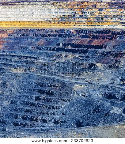 Close Up Of Quarry Extracting Iron Ore With Heavy Trucks, Excavators, Diggers And Locomotives
