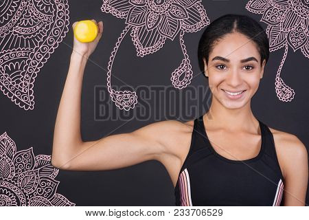 Showing Muscles. Cheerful Young Smiling Sportswoman Looking Strong While Holding A Little Yellow Han