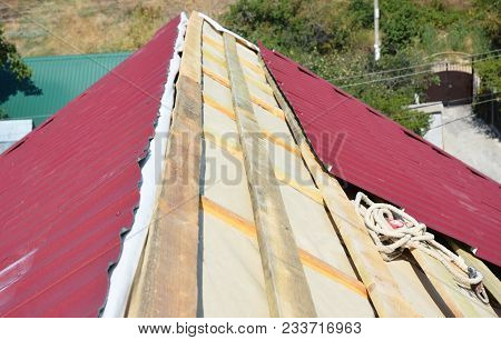 Roofing Contractors Installing House  Metal Sheets Roof.  Metal Roofing Construction. Metal Roof Rep
