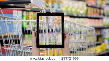 Digital composite of Hand taking picture of shopping cart with tablet PC in grocery store