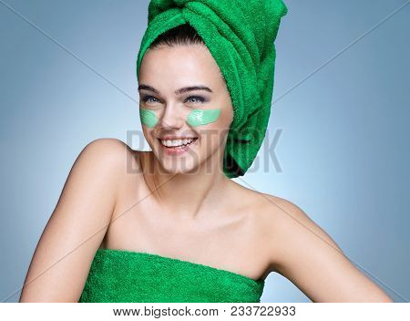 Smiling Girl In Green Towels With Moisturizing Cream On Her Face. Photo Of Young Girl With Flawless