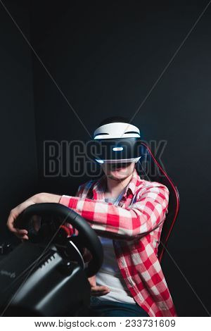 Gamer Plays Racing In Vr Glasses On A Car Simulator. A Man With Glasses Of Virtual Reality Plays A G